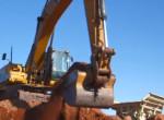 CAT backhoe pulling up red dirt